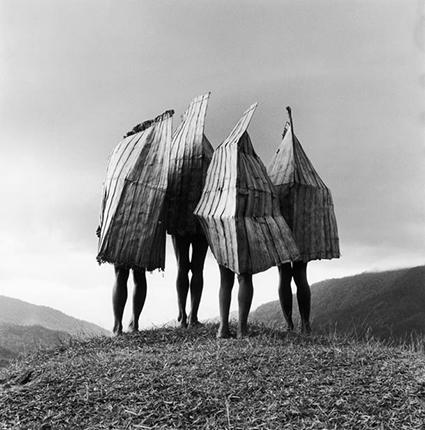 "1994, Irian Jaya, Indonesia --- In Irian Jaya, four Mek tribesman stand on a hilltop wearing ""rain gear."" --- Image by © Chris Rainier/CORBIS"